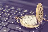 istock Vintage gold pocket watch on a black laptop keyboard 1284178894