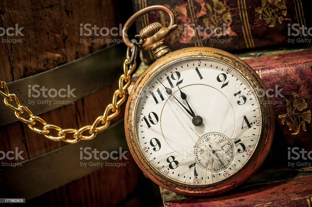 Vintage gold pocket watch on books stock photo