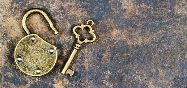 istock Vintage golden key and unlocked padlock on a rusty metal background, escape room concept 1203988623