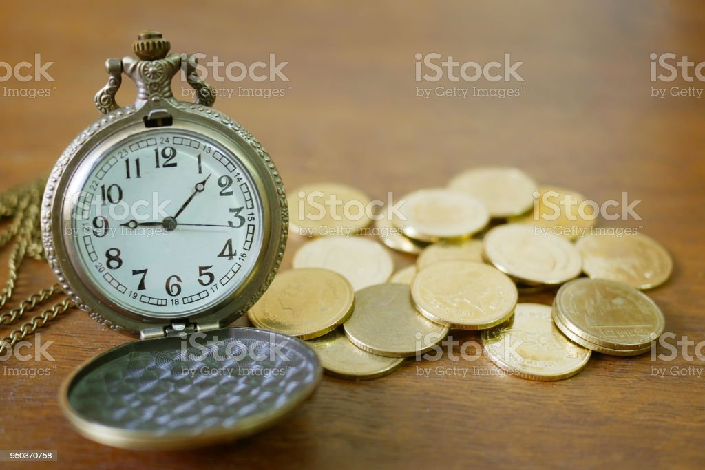 vintage golden pocket watch with stack  on wood table background stock photo
