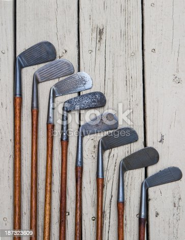 an assortment of genuine hickory shafted golf clubs on a weathered and rough surface