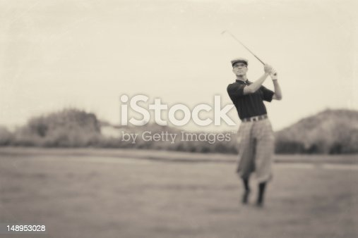 A male golfer in knickers goes for the green. Vintage processing.
