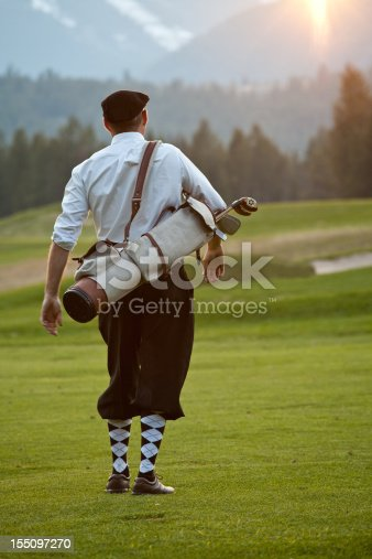 A golfer with classic golf outfit. Plus fours. Vintage fashion.Vertical colour image. Golfer in his early 40s, fit and athletic, carrying an old leather golf bag with classy golf attire. Argyle socks, white dress shirt, and fashionable black cap complete the elegant look. A common fashion scene from the 1920s, during the golden age of golf. Model is Caucasian and unrecognizable.