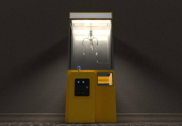 Vintage Grabber Machine A yellow empty arcade type claw grabber game in a dimly lit vintage room - 3D render claw stock pictures, royalty-free photos & images