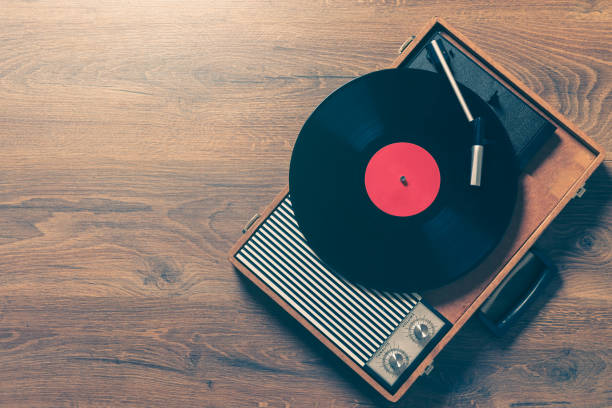 Vintage gramophone with a vynil record Retro Gramophone with a vinyl record on wooden table, top view and copy space,vintage style with split toning. album stock pictures, royalty-free photos & images