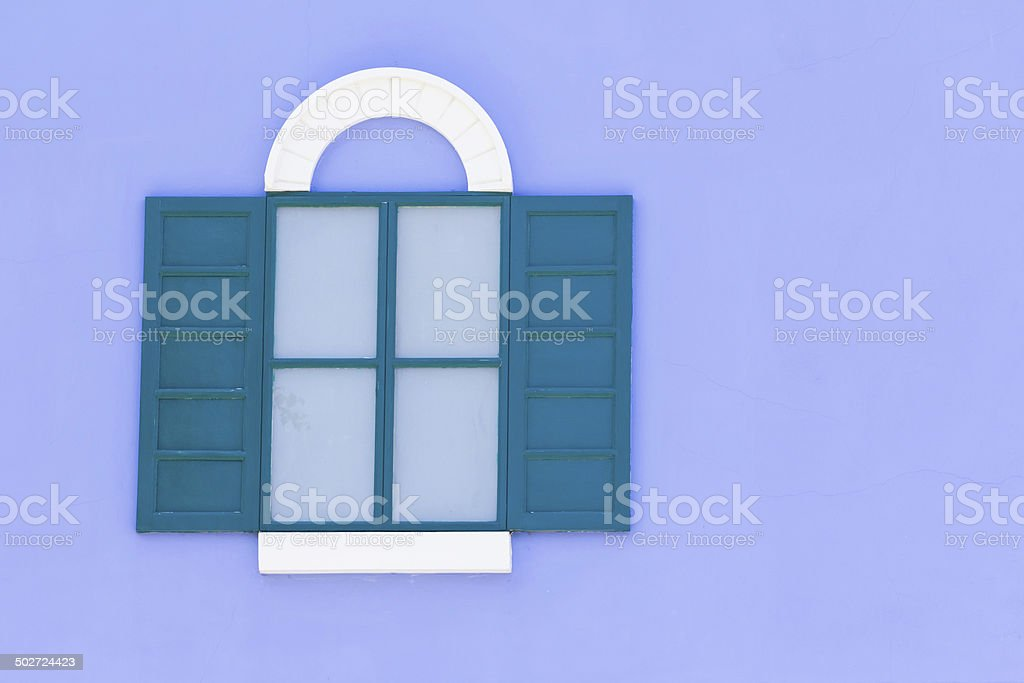 Vintage green and white window on purple brick wall royalty-free stock photo
