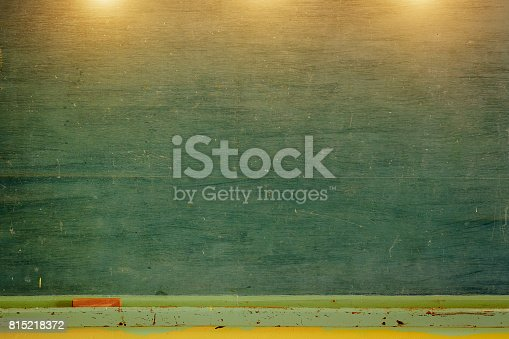 istock Vintage green chalkboard with eraser and chalk rubbed out on blackboard. Horizontal composition with copy space 815218372