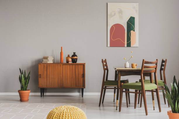 Vintage grey dining room with abstract paintings and wooden cupboard – zdjęcie