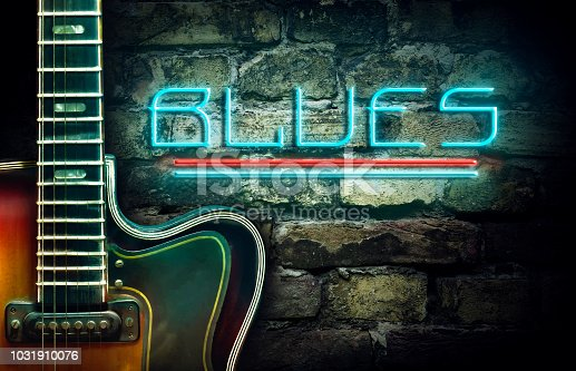 Vintage guitar and a neon inscription JBlues on the background of an old brick wall. Concept music. Musical background.