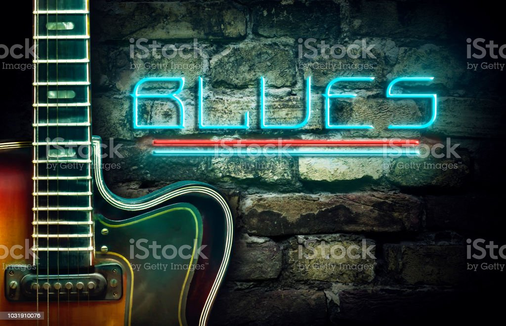 Vintage guitar and a neon inscription Blues on the background of an old brick wall. Concept music. stock photo