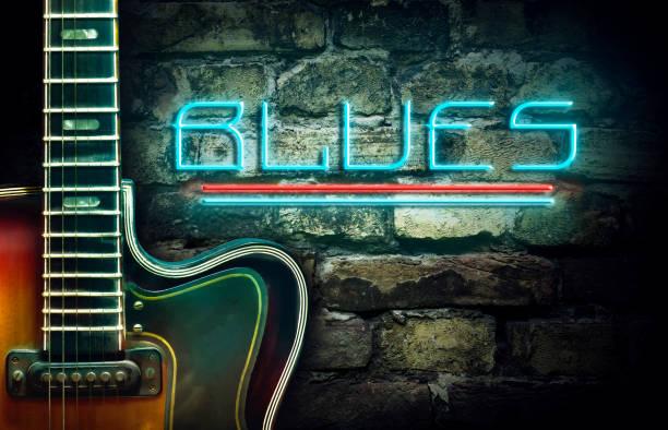 vintage-gitarren und eine neon-inschrift blues auf dem hintergrund einer alten backstein-mauer. konzept-musik. - blues stock-fotos und bilder