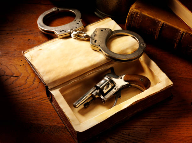 vintage handgun and handcuffs - murder mystery stock photos and pictures