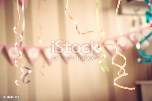 istock Vintage happy birthday party blurred background with hanging ribbons and garland in decorated room in pastel colors 691634034