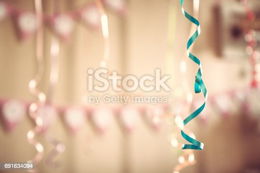 istock Vintage happy birthday party defocused background with hanging ribbons and garland in decorated room in pastel colors 691634094