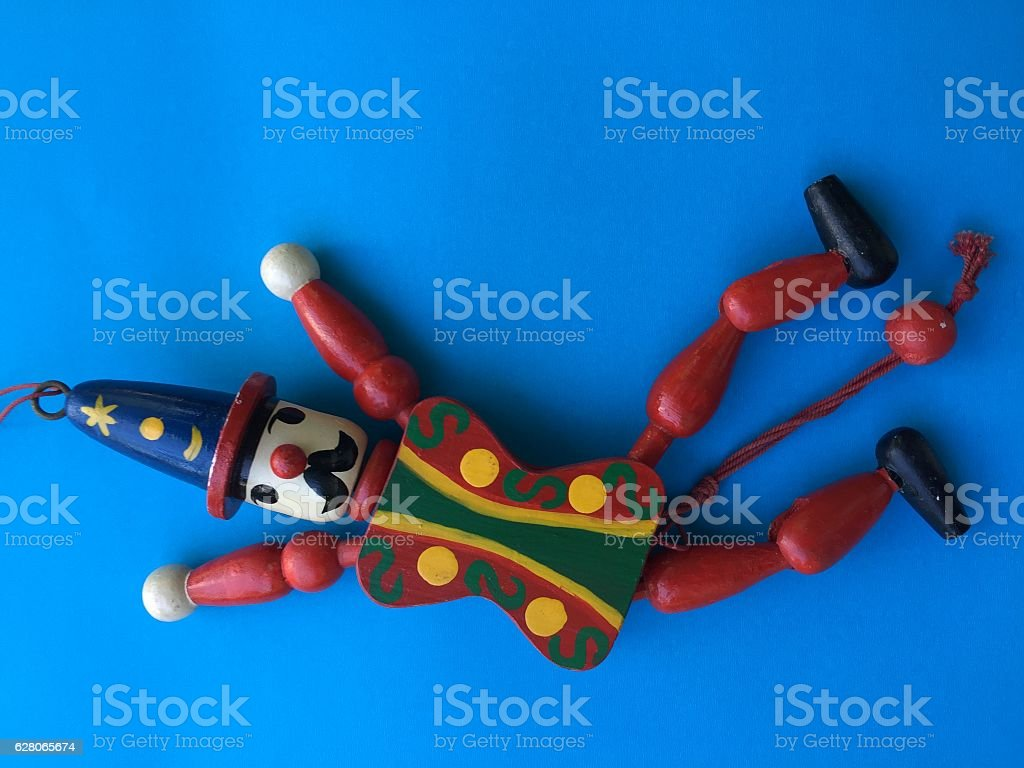 Vintage Harleqin crown wood doll toy on blue background stock photo