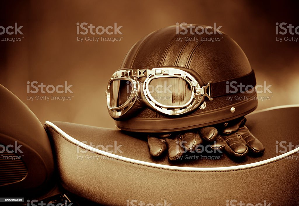 Vintage helmet and gloves on a motorcycle seat stock photo