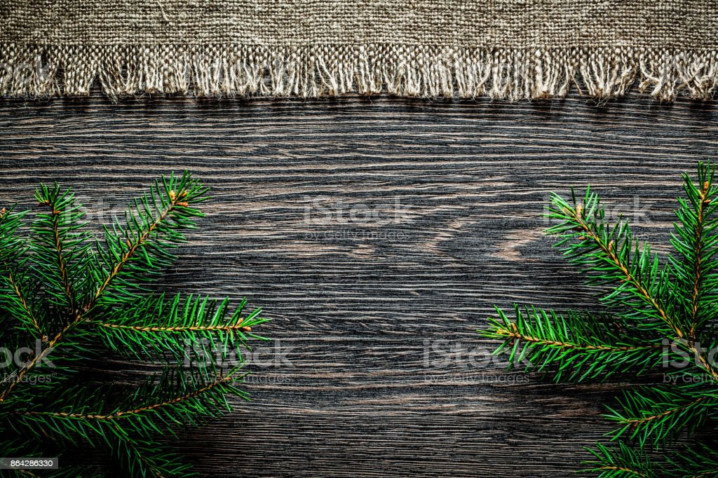 Vintage hessian fir branch on wooden board Christmas background royalty-free stock photo