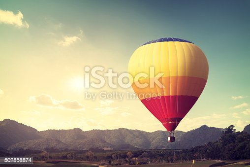 Hot air balloon over mountain, vintage retro filter effect