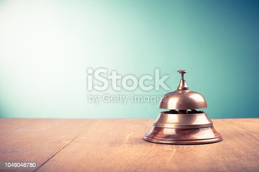 istock Vintage hotel reception service desk bell. Old retro style filtered photo 1049046780