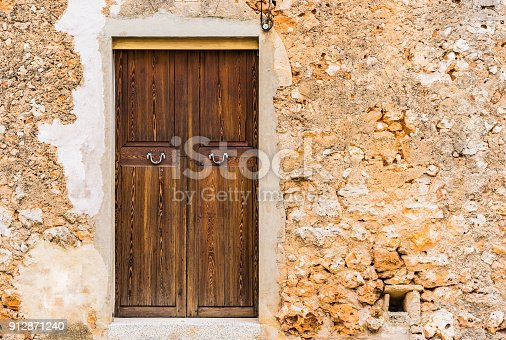 Old house wooden front door with ancient stone wall background