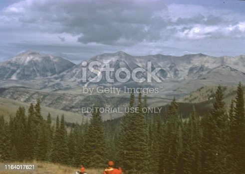 United States - January 01, 1965:  Vintage, authentic archival photograph of two hunters wearing high visibility safety jackets at bottom of frame looking at wilderness landscape, 1965