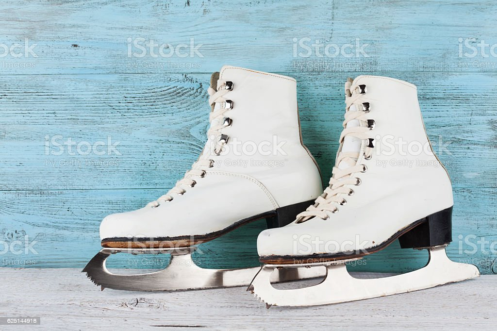 Vintage ice skates for figure skating on turquoise background. Sport...