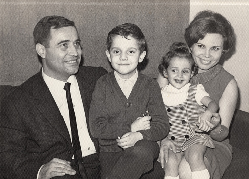 Vintage image made in the 60s: Smiling mature couple posing with their children sitting in their living room couch