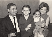 istock Vintage image made in the 60s: Smiling mature couple posing with their children 1318558633