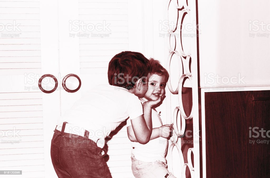 Vintage image of a boy kissing his little sister stock photo