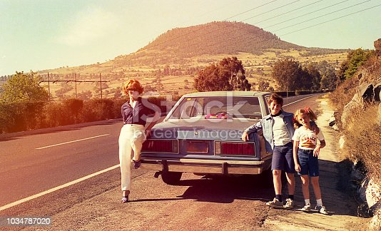 Vintage image of a mother and her children at a stop on the road.