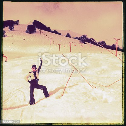 Vintage image fromthe seventies of a woman posing funny in the middle of a ski track.