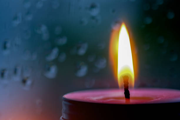 imagen vintage de luz de la vela rosa en el frente en ventana con gotas de lluvia borrosa y fondo bajo luz natural - adviento fotografías e imágenes de stock