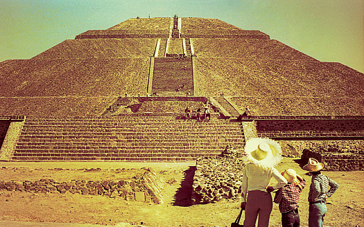 Vintage yelow toned image of a family looking at the The Pyramid of the Sun in Teotihuacan during a trip to Mexico