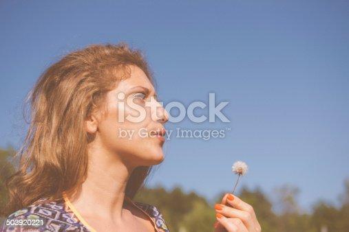 Woman blowing dandellion in nature, image desaturater, polaroid look, grain added
