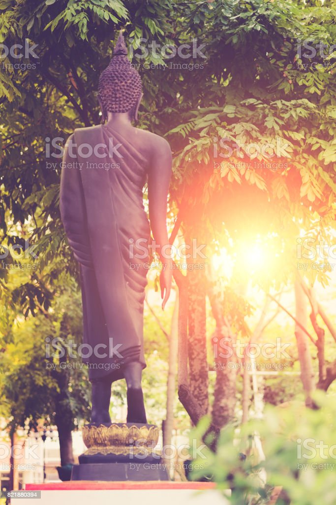 Vintage image style ,Back view on the standing Buddha statue of temple garden in Bangkok, Thailand stock photo