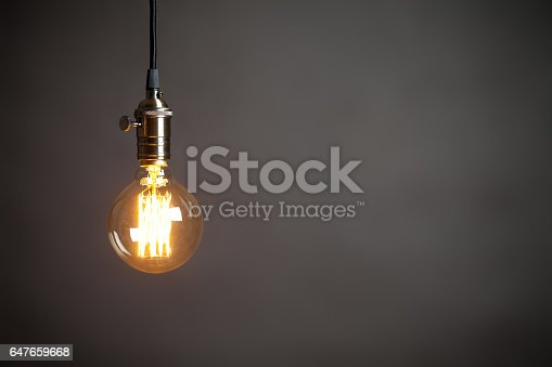 Vintage incandescent Edison type bulb on grey wall. On right is empty space to put text or something else. This file is cleaned and retouched.