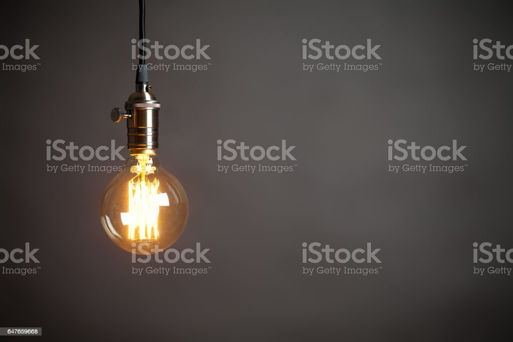 Vintage incandescent Edison type bulb on grey wall stock photo