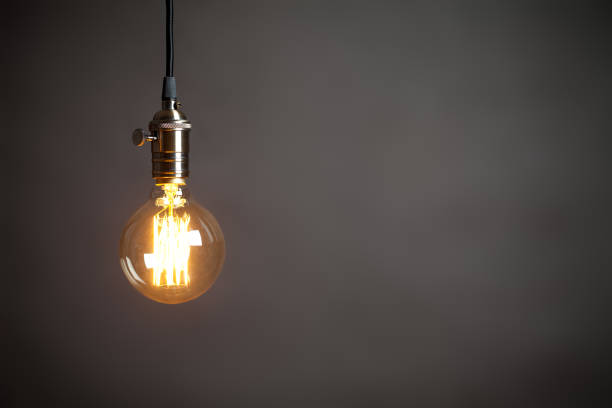vintage incandescent edison type bulb on grey wall - light bulb stock pictures, royalty-free photos & images