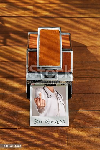 Vintage instant film camera and a printed christmas ornament photograph with Bye bye 2020 note on it on wooden table under afternoon sunlight. Bye bye to old year concept