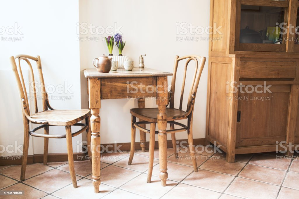 Vintage Interior Design Of Kitchen Space With Small Table Against White Wall With Simple Chairs And Plant Decorations Minimalistic Concept Of Kitchen Space Stock Photo Download Image Now Istock
