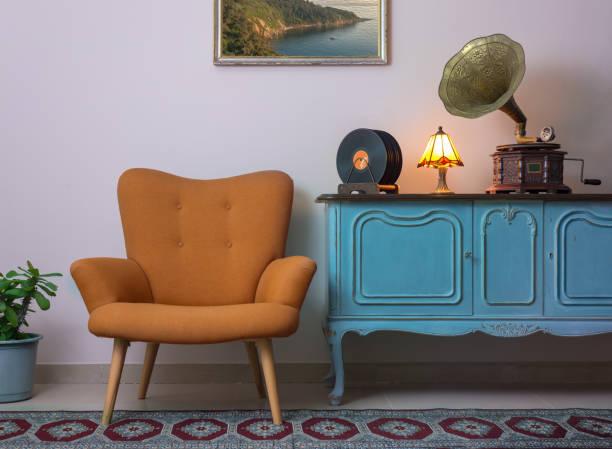vintage interieur des retro-orange sessel, vintage leichte blaue anrichte aus holz, alte plattenspieler (gramophone), vinyl-schallplatten und beleuchtete tischleuchte - teppich hellblau stock-fotos und bilder