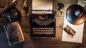 Vintage journalist desktop with typewriter and retro lamp, 1950s style, flat lay desktop