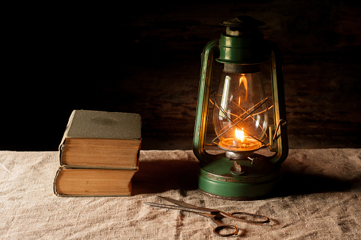 Vintage kerosene lamp and antique books on the linen tablecloth.