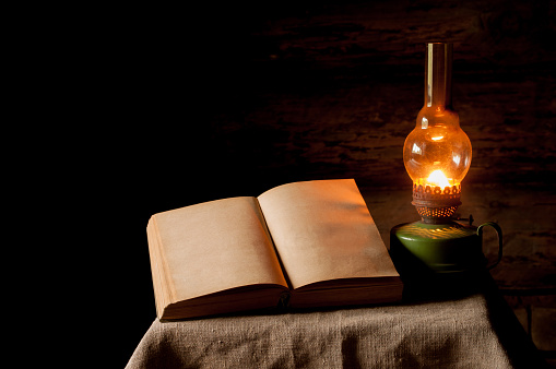 Vintage kerosene lamp and open book on the linen tablecloth.