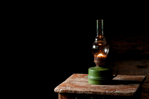 vintage kerosene lamp on the wooden stool
