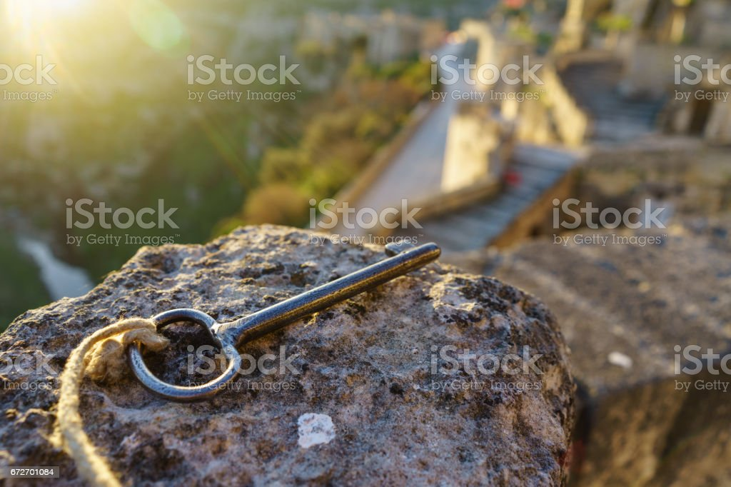 Vintage key on the stone with sun light in the morning as key to heaven concept stock photo