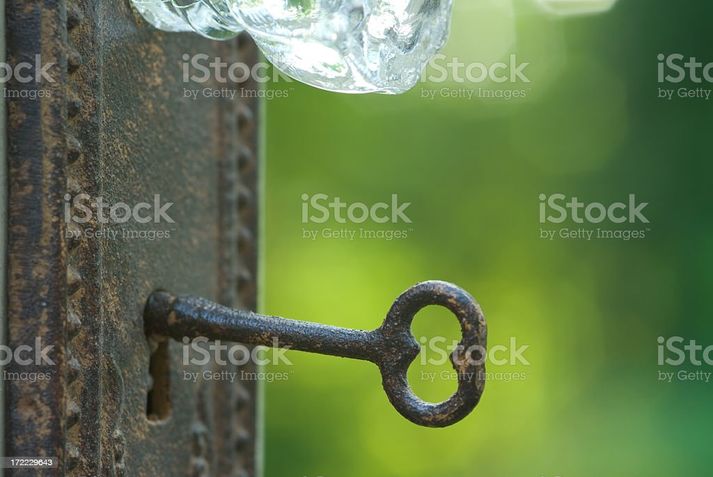 Vintage key unlocking a door outside with crystal doorknob stock photo