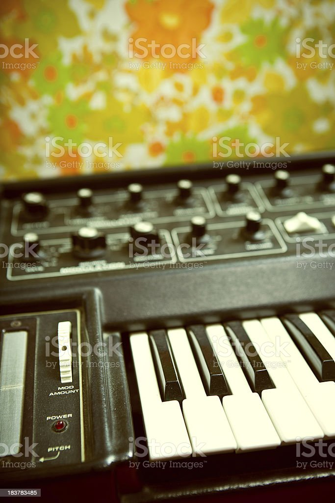 Vintage Keyboard Synthesizer With Floral Wallpaper Stock Photo