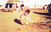 vintage and burnt color image of a little boy playing in the beach.