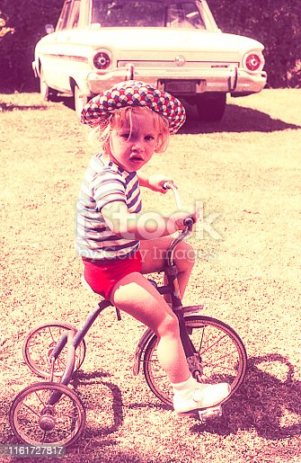 Vintage kid riding on a tricycle outdoors.